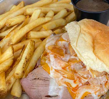 Sliced pork sandwich with cheese and fries